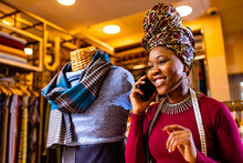 Tanzanian Woman With Snake Print Turban Over Hear Working In Fabrics Shop Calling To Client By Smartphone