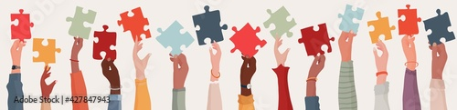 Foto Group of multi-ethnic business people with raised arms holding a piece of jigsaw