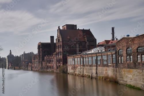 Stare po przemysłowe budynki nad brzegiem rzeki w mieście Szczecin - fototapety na wymiar