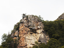 Steep Cliffs Covered With Green Vegetation Against The Backdrop Of A White Cloudy Sky