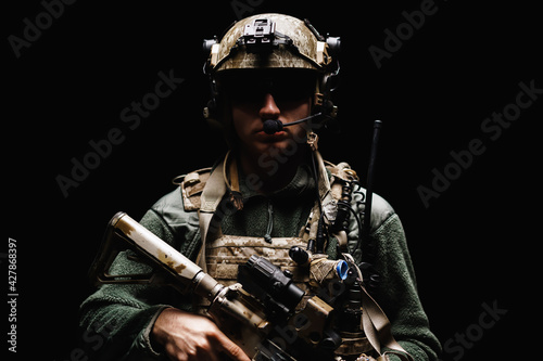 Fotografering Special forces soldier with rifle on black background