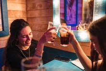 Dos Chicas En Un Bar Brindando Con Refresco