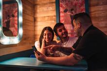 Tres Amigos, Dos Chicos Y Una Chica Mirando Smartphone Y Tomando Selfies En Un Bar De Decoración Circense