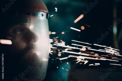 Obraz na plátně Man welder grinder in transparent protective mask with flying sparks in darkness