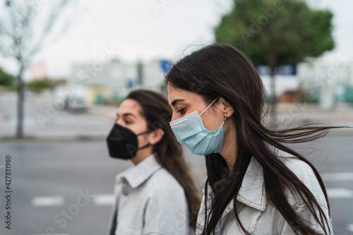 Dos amigas con chaqueta vaquera paseando con mascarilla por la calle Fototapeta