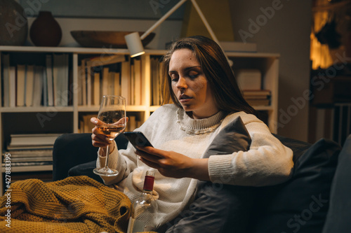 Obraz na plátně depressed woman drinking wine sitting on sofa at home