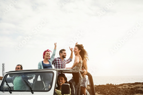 Obraz Group of happy friends doing excursion on beach in convertible 4x4 car- Soft focus on top man face - fototapety do salonu