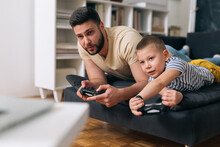 Father And Son Playing Video Games At Home