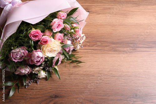 Obraz Beautiful bouquet with roses on wooden table. Space for text - fototapety do salonu