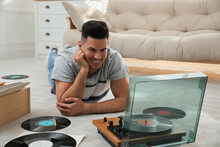 Man Listening To Music With Turntable While Lying On Floor At Home