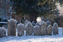 A Row Of Old Gravestones Covered In Snow In A Churchyard