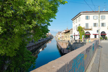 Perspective Of Famous Old Navigli Neighborhood In Milan, Italy, Looking Like A River. Green Tree In The Foreground, Buildings And Blue Sky In The Background.