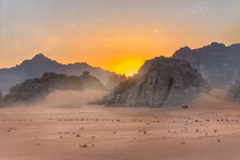 A Magical Sunset And Star Trails Over The Golden Sand Of Wadi Rum - Jordan.