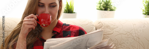 woman drinking coffe and reading sit on sofa