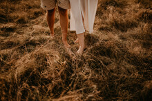 Tanned Man And Light Skin Legs Woman Barefoot Close-up Walking On Dry Green Thin Grass.
