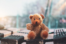 Happy Teddy Bear With Smiling Face Sitting On Wooden Bridge On Sunny Day Summer, Brown Bear Doll Sitting Alone In Outdoors Playground With Blurry Bokeh Of Morning Sunlight Background On Spring