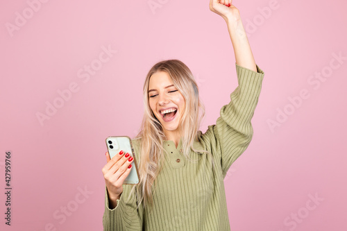 Canvas Print Pretty european woman in casual knitted sweater on pink background look on mobil