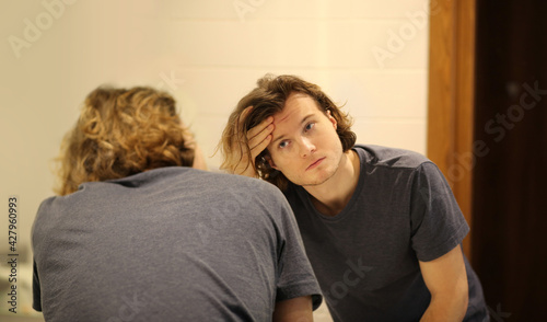 young man looking in the mirror,combing his hair,looking at problems on face. - fototapety na wymiar