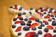 Tarta na kruchym cieście z bitą śmietaną i owocami - truskawkami i borówkami
