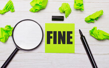 The Word FINE Written On A Green Sticky Note Next To A Magnifying Glass And A Black Marker On A Wooden Table
