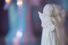 Small White Marble Figurine Of An Angel On A Pearlescent Pink Blue Blurred Bokeh Background. Place For Text