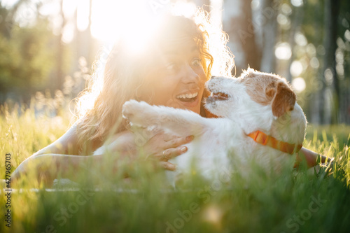 Photo Surprised girl playing with her dog Jack Russell in the park at dawn