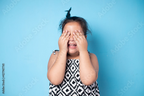 Canvas Portrait of surprised cute little toddler girl child standing isolated over blue background