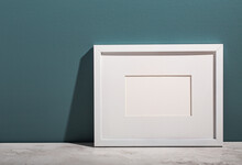 A White Picture Frame Leans On An Aegean Teal Painted Wall.