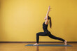 Attractive woman in black sportswear practicing yoga performs Virabhadrasana exercise, warrior pose 1, against a yellow wall with copy space