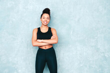 Fitness Smiling Black Woman In Sports Clothing With Afro Curls Hairstyle.She Wearing Sportswear. Young Beautiful Model With Perfect Tanned Body.Female With Crossed Arms In Studio Near Gray Wall
