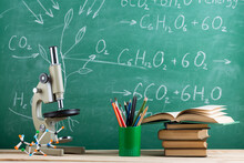 Education And Sciences Concept - Books, Molecule Model And Microscope On The Desk In The Auditorium, Chalkboard Background.