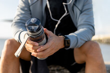 Man Runner Is Holding Bottle Of Water. Tired Man Is Drinking Water After Run Exercise.