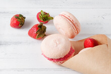 Fruit Cookies Pink Macaroons With Fresh Strawberries Spill Out Of A Paper Bag On A White