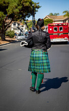 Female Bagpipe Player In A Kilt Walking Behind A Fire Truck