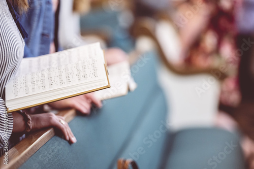 Fotografie, Obraz Church choir members holding sheet music and singing during a rehearsal