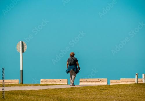 Billede på lærred mujer caminando por un camino al cielo