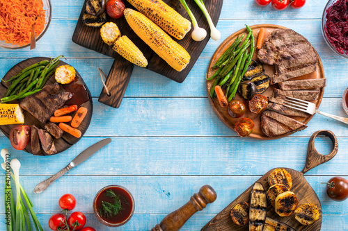 Fotografiet Grilled beef steak with grilled vegetables on wooden blue table