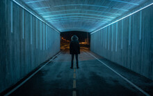 Full Length Of Man Standing In Illuminated Tunnel