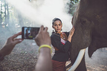 Cropped Hand Of Person Photographing Woman With Elephant In Forest