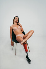 Young Woman In Lingerie With Prosthetic Leg Relaxing Over Gray Background