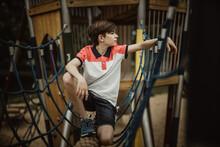 Full Length Of Boy Crouching On Jungle Gym