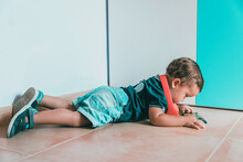 Boy Lying On Floor Against Wall At Home