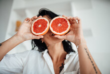 Woman Holding Grapefruit Slice At Home