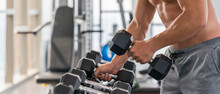 Athletic Bodybuilder Man Lifting Dumbbell From Rack In Gym And Fitness Club