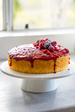 Lemon Raspberry One Layer Cake On A Cake Stand On A Window Sill