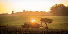Ploughing A Field At Sunset With A Tractor And Plough, Ready For Crops On A Farm