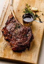 Barbecue Grilled Tomahawk Steak On Bone On Wood Serving Board