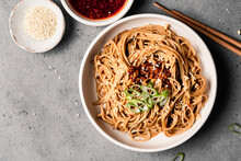 Spicy Sesame Noodles In A Bowl Next To Chile Oil And Sesame Seeds.