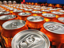 Selective Focus Shot Of Shiny Orange Cans Production Line At A Factory