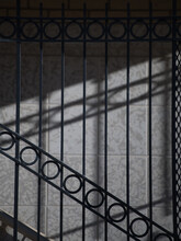 Black And White Shadows Of Vertical Lines And Circles Of Exterior Wrought Iron Stair Railing Cast Onto Brick Building In Morning Sunlight Outdoors In Urban Environment Vertical Format